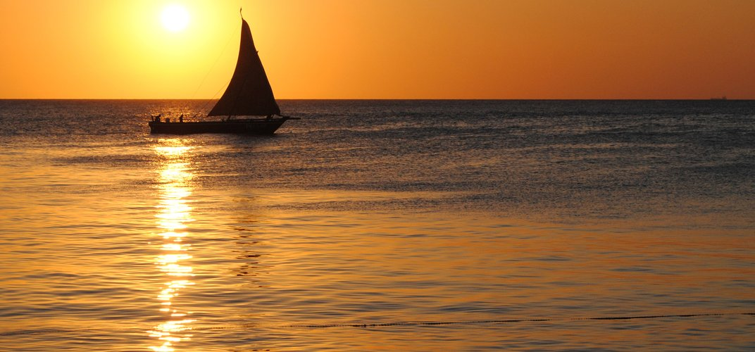 Sunset with traditional <i>dhou>/i> on the water off Zanzibar's Stone Town
